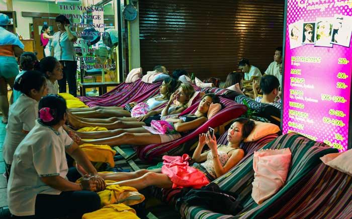 Massagistas atendendo clientes na rua em Bangkok