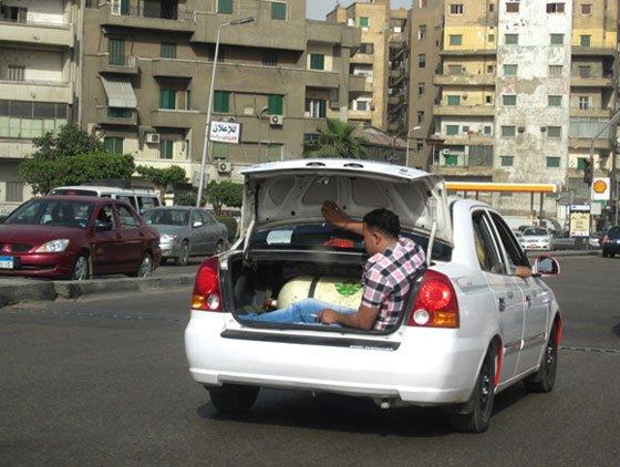 homem andando no bagageiro de carro egito